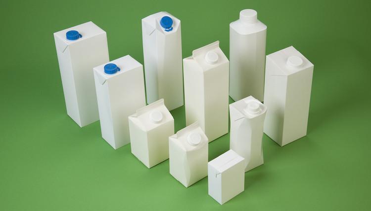 Weiße Kartons auf gruenem Grund